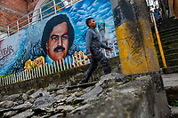 "A Colombian boy walks along a large mural artwork, depicting the drug lord Pablo Escobar, painted on the wall in the Pablo Escobar neighborhood in Medellín, Colombia, 30 November 2017. Twenty five years after Pablo Escobar's death, the legacy of the Medellín Cartel leader is alive and flourishing. Although many Colombians who lived through the decades of drug wars, assassinations, kidnappings, reject Pablo Escobar's cult and his celebrity status, there is a significant number of Colombians who admire him, worshipping the questionable ""Robin Hood"" image he had. Moreover, in the recent years, the popular ""Narcos"" TV series has inspired thousands of tourists to visit Medellín, creating a booming business for many but causing a controversial rise of narco-tourism."