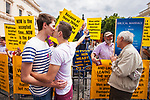 © Joel Goodman - 07973 332324 . 02/07/2011 . London , UK . Boyfriends Robert Waldon, 18 (left) and Ben Kennedy, 17 (right) from Essex, share a kiss and stick a finger up in protest to protesting Evangelical Christians . Tens of thousands take part in the annual Pride march in London . Photo credit : Joel Goodman