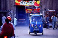 Motorcycleriksha on the street in front of the Deli Gate, one entry to the old town of Lahore. In the back, advertising of Coka Cola.<br /> 18.2.2001, Lahore/Pakistan<br /> Copyright: Christian-Ditsch.de<br /> [Inhaltsveraendernde Manipulation des Fotos nur nach ausdruecklicher Genehmigung des Fotografen. Vereinbarungen ueber Abtretung von Persoenlichkeitsrechten/Model Release der abgebildeten Person/Personen liegen nicht vor. NO MODEL RELEASE! Nur fuer Redaktionelle Zwecke. Don't publish without copyright Christian-Ditsch.de, Veroeffentlichung nur mit Fotografennennung, sowie gegen Honorar, MwSt. und Beleg. Konto: I N G - D i B a, IBAN DE58500105175400192269, BIC INGDDEFFXXX, Kontakt: post@christian-ditsch.de<br /> Bei der Bearbeitung der Dateiinformationen darf die Urheberkennzeichnung in den EXIF- und  IPTC-Daten nicht entfernt werden, diese sind in digitalen Medien nach §95c UrhG rechtlich geschuetzt. Der Urhebervermerk wird gemaess §13 UrhG verlangt.]