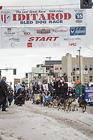 John Baker and team leave the ceremonial start line with an Iditarider at 4th Avenue and D street in downtown Anchorage, Alaska during the 2015 Iditarod race. Photo by Jim Kohl/IditarodPhotos.com