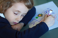 Four year old girl falls asleep in the middle of drawing, France.