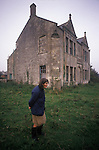 Francis Parfitt outside Spargrove Manor House, just been feeding the animals they farm. Parfitt Sisters Story, Spargrove Manor, Batcombe, Somerset. Taken for the Sunday Times Magazine 1988. Used December 1988.