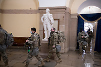 National Guard troops enter the Crypt at the U.S. Capitol, as the House of Representatives vote on H. Res. 24, Impeaching Donald John Trump, President of the United States, for high crimes and misdemeanors, at the U.S. Capitol in Washington, DC, Wednesday, January 13, 2021. Credit: Rod Lamkey / CNP /MediaPunch