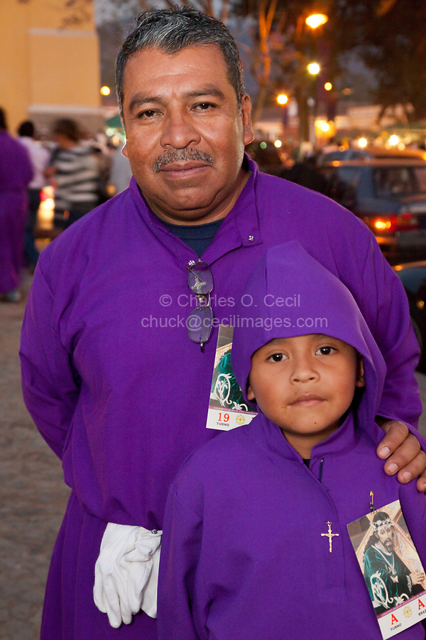 Antigua, Guatemala.  Father and Son Relax after doing their Shifts as Cucuruchos, Carrying a Float (Anda) in a Religious Procession during Holy Week, La Semana Santa.
