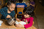Preschool 3-4 year olds meal time girl pouring milk for another child