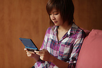 August 2012 - Montreal (Qc) CANADA - MODEL RELEASE photo of a 19 year old asian (Vietnamese) female teen <br /> paying video game
