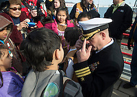 130501-N-DR144-444 COOK INLET, Alaska (May 1, 2013)- Commanding Officer Cmdr. Joel Stewart answers questions about his uniform from Alaska Native children during a welcoming ceremony for San Antonio-class amphibious transport dock ship USS Anchorage (LPD 23) at the Port of Anchorage. Anchorage arrived at its namesake city of Anchorage, Alaska for its commissioning ceremony scheduled to take place May 4. (U.S. Navy photo by Mass Communication Specialist 1st Class James R. Evans / RELEASED)