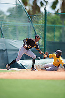 Pittsburgh Pirates Alfredo Reyes (12) tags out Michael da la Cruz (64) on a double steal attempt during an Instructional League Intrasquad Black & Gold game on September 20, 2016 at Pirate City in Bradenton, Florida.  (Mike Janes/Four Seam Images)