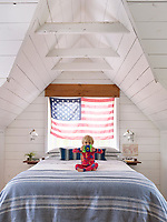 The upstairs loft houses the white, wood panelled master bedroom. The room is light and airy with its vaulted ceiling and the simple blue and white theme gives the space a cool feel.