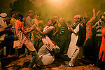 Divotees dance at Radha Raman Mandir during Holi Festival. Holi - The  Hindu festival of colour is celibrated for a week in the Brraj region of Uttar Pradesh, India.