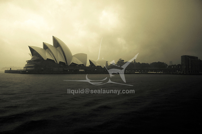 Arrival at Circular Quays by a Sydney Ferries coming from Manly  passing close by the Opera House, early in the morning under the rain.