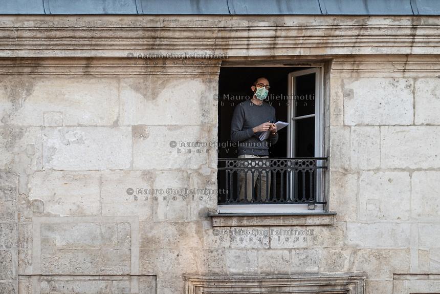 uomo  con mascherina alla finestra  a parigi