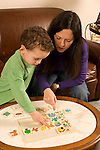mother and 3 year old son playing with wooden sequencing puzzle toy Caucasian vertical