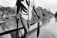 Uganda. West Nile. Adjumani. Fishermen and pirogues on White Nile river. A man holds a fish in his left hand and a machete in his right hand. The White Nile is a river, one of the two main tributaries of the Nile. West Nile sub-region (previously known as West Nile Province and West Nile District) is a region in north-western Uganda. © 1989 Didier Ruef