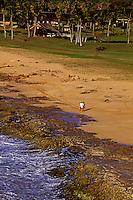 A couple strolls along the coral shoreline of Kepuhi beach on west Molokai.