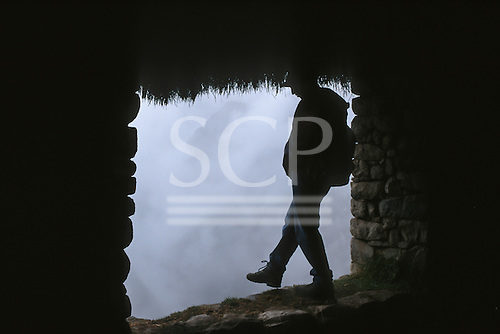 Inca Trail, Peru. Trekker stepping out of a window in the ruined city of Machu Picchu into the clouds.