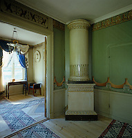 In the corner of the dining room stands a tiled stove and the hand-painted wallpaper and frieze transform the plain coloured room into a simulacrum of draped cloth