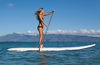 Fit, athletic woman standup paddling at Napili Bay, Maui, with Molokai in the distance.
