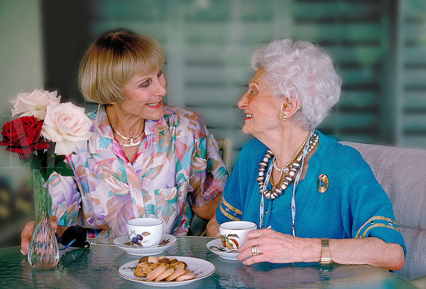 Mature mother and daughter sharing tea and biscuits.