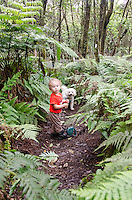 A young part-Asian local boy with his dog pause along the native forest loop trail at Kalopa State Park, Hamakua Coast, Big Island.