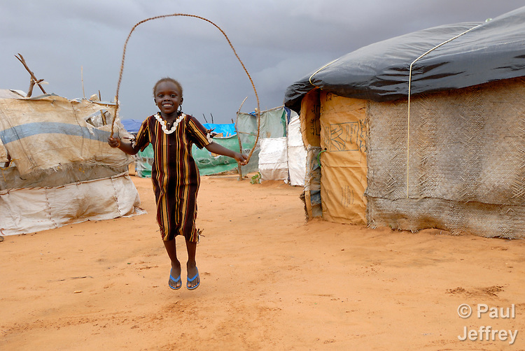 A girl skips rope in the Dereig Camp for internally displaced persons, one of many such settlements for people displaced by the violence in Darfur.
