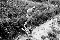 Switzerland. Canton Valais. Hèrens valley. Arbey. A young angry boy, wearing a ski helmet on his head and carrying a plastic gun's toy in his hand, throws a stone. Towering rage. Children' game. Swiss alpine farmers. Alps mountains peasants.  © 1994 Didier Ruef