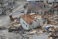 A house lies upended among debris following an 8.9-magnitude earthquake, which triggered a devastating tsunami through this Japanese coastal city. Teams from the United States, United Kingdom and China are on scene to assist in searching for missing residents.