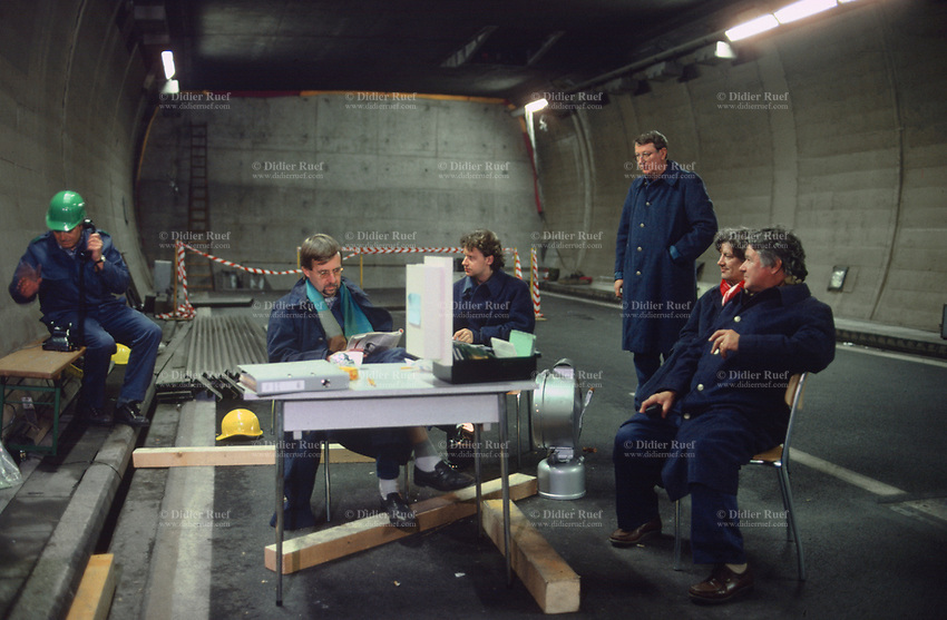 Switzerland. Canton Lucerne. A group of bored men seat and wait in the Sonnenberg tunnel in Lucerne during the largest civil defense exercise ever held in the country. The highway has been locked with an armor plate door. From 16 to 21 November 1987, almost 1200 men and women converted a motorway tunnel into perhaps the world's largest bunker structure. The civil protectors had to prove during the exercise «Ameise» ( Ants in english) that in an emergency more than 20,000 inhabitants of the city of Lucerne could survive here in the mountain for two weeks. The Sonnenberg Tunnel is a 1,550m  long motorway tunnel, constructed between 1971 and 1976. At its completion it was also the world's largest civilian nuclear fallout shelter, designed to protect 20,000 civilians in the eventuality of war or disaster. Based on a federal law from 1963, Switzerland aims to provide nuclear fallout shelters for the entire population of the country. The construction of a new tunnel near an urban centre was seen as an opportunity to provide shelter space for a large number of people at the same time. The giant bunker was built between 1970 and 1976 at a cost of 40 million Swiss francs. The shelter consisted of the two motorway tunnels (one per direction of travel), each capable of holding 10,000 people in 64 person subdivisions. A seven story cavern between the tunnels contained shelter infrastructure including a command post, an emergency hospital, a radio studio, a telephone centre, prison cells and ventilation machines. The shelter was designed to withstand the blast from a 1 megaton nuclear explosion 1 kilometer away. The blast doors at the tunnel portals are 1.5 meters thick and weigh 350 tons. The logistical problems of maintaining a population of 20,000 in close confines were not thoroughly explored, and testing the installation was difficult because it required closing the motorway and rerouting the usual traffic. The only large-scale test, a five-day exercise in 1987 to pra