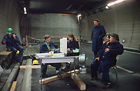 Switzerland. Canton Lucerne. A group of bored men seat and wait in the Sonnenberg tunnel in Lucerne during the largest civil defense exercise ever held in the country. The highway has been locked with an armor plate door. From 16 to 21 November 1987, almost 1200 men and women converted a motorway tunnel into perhaps the world's largest bunker structure. The civil protectors had to prove during the exercise «Ameise » ( Ants in english) that in an emergency more than 20,000 inhabitants of the city of Lucerne could survive here in the mountain for two weeks. The Sonnenberg Tunnel is a 1,550 m  long motorway tunnel, constructed between 1971 and 1976. At its completion it was also the world's largest civilian nuclear fallout shelter, designed to protect 20,000 civilians in the eventuality of war or disaster. Based on a federal law from 1963, Switzerland aims to provide nuclear fallout shelters for the entire population of the country. The construction of a new tunnel near an urban centre was seen as an opportunity to provide shelter space for a large number of people at the same time. The giant bunker was built between 1970 and 1976 at a cost of 40 million Swiss francs. The shelter consisted of the two motorway tunnels (one per direction of travel), each capable of holding 10,000 people in 64 person subdivisions. A seven story cavern between the tunnels contained shelter infrastructure including a command post, an emergency hospital, a radio studio, a telephone centre, prison cells and ventilation machines. The shelter was designed to withstand the blast from a 1 megaton nuclear explosion 1 kilometer away. The blast doors at the tunnel portals are 1.5 meters thick and weigh 350 tons. The logistical problems of maintaining a population of 20,000 in close confines were not thoroughly explored, and testing the installation was difficult because it required closing the motorway and rerouting the usual traffic. The only large-scale test, a five-day exercise in 1987 to pra