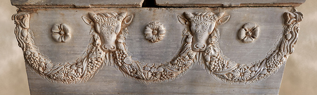 Roman relief sculpted garland sarcophagus with reliefs of bulls heads and garlands, 2nd century AD. Adana Archaeology Museum, Turkey. Against a warm art background