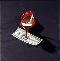 Woman's high heel shoe sitting on one hundred dollar bill
