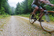 Man biking on Rob Brook Road in Albany, New Hampshire USA. This dirt road follows parts of the old Bartlett and Albany Railroad which was a logging railroad in operation from 1887 - 1894.