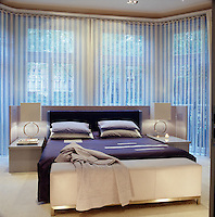 The master bed has an integral headboard and bedside tables and the bay window is hung with blue and white fringing