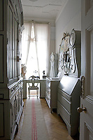 The small study/home office is dominated by a vast wooden cupboard and has a desk tucked in front of the window