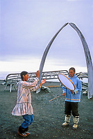 Native Alaska dancers, Bowhead whale bone arches and umiak (whale boat) skeletons, Arctic ocean beach, Utqiagvik (Barrow), Alaska
