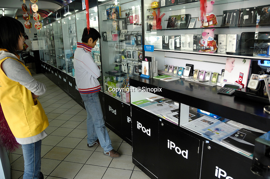 Customers browsing in an Apple iPOD store in Beijing, China. .