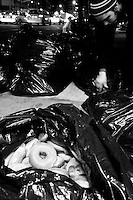 Adam Weissman searches through trash bags outside a New York City deli for consumable food on April 5, 2006.