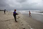 A fisherman hauls in a net on a stormy winter day in Da Nang, Vietnam. Dec. 23, 2012.