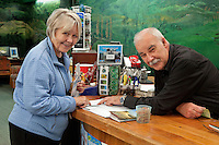 Tirau, New Zealand.  Foreign Tourist (left) getting information at government iSite, a tourist information office.