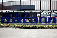 Employees at Hon Hai's Foxconn plant peek out from the back of a company sign in Shenzhen, China. Hon Hai is the parts supplier for many hi-tech companies around the world including Apple Inc., Hewlett-Packard Co. and Dell Inc. There have been 12 suicides at the company's 300 thousand employee strong factory complex in Shenzhen so far this year..26 May 2010