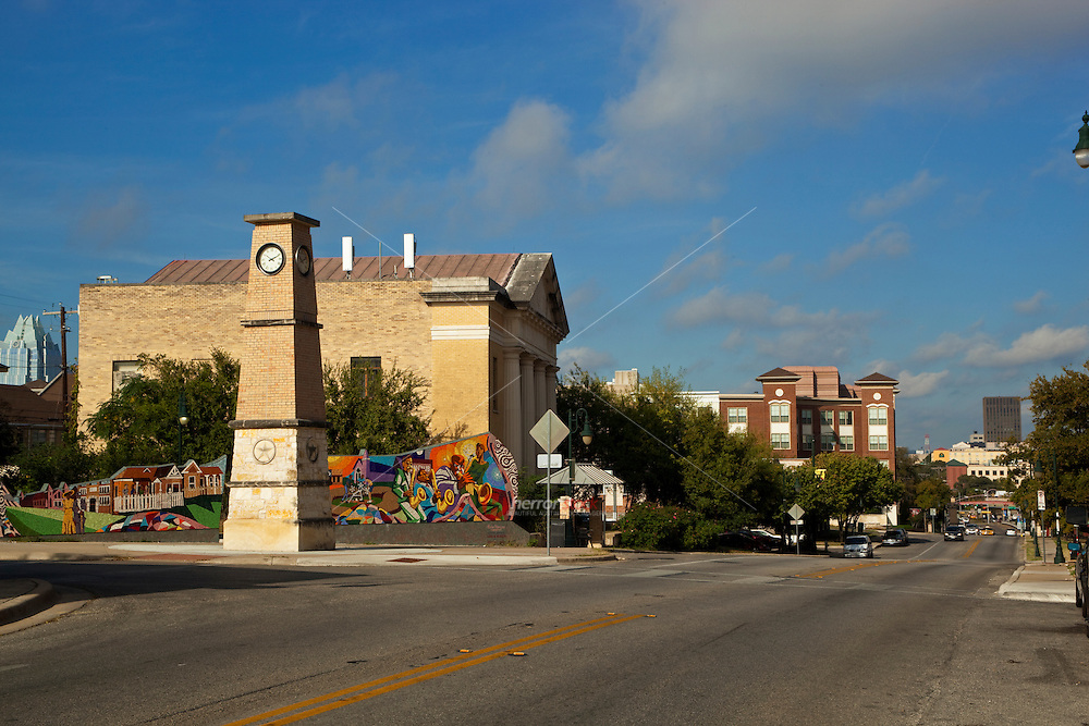 East Austin Urdy Plaza Clock Tower features a mural commissioned by the ARA runs along a corner at Waller and East 11th streets, illustrating the history of the area in bits of broken tile. A clock tower stands near a star-lined brick-and-metal archway that spans the street.