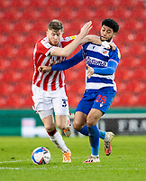 6th February 2021; Bet365 Stadium, Stoke, Staffordshire, England; English Football League Championship Football, Stoke City versus Reading; Nathan Collins of Stoke City and Josh Laurent of Reading challenge for a loose ball
