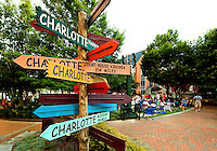 "Photo of the iconic Charlotte signs statue/public art located on The Green in Uptown Charlotte. The Green, actually the top level of an underground parking garage, is a tiered outdoor space with a lawn, lush gardens, interactive fountains and abundant public art. Contemporary artist Gary Sweeney, based in San Antonio, created the piece named ""Charlotte - The Center of the Known World."" The signs point to 11 other areas also named Charlotte. The signs point to the approximate direction of the locales they identify and the distance to each. Photo taken during the 2012 Charlotte Shakespeare Festival. .."