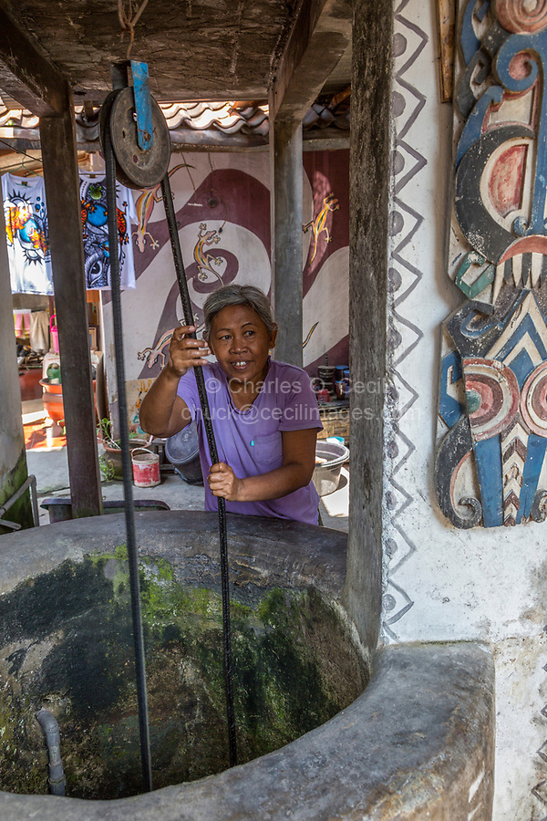 Yogyakarta, Java, Indonesia.  Woman Drawing Water from her Private Well in Neighborhood Family Home.
