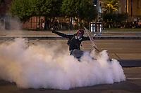 BOGOTA - COLOMBIA, 25-05-2021: Un manifestante de primera línea patea un gas lacrimógeno lanzado por el ESMAD (Escuadrón Móvil Antidisturbios de la Policía) durante los disturbios en el sector de las Américas de la ciudad de Bogotá durante el día 28 del Paro Nacional en Colombia hoy, 25 de mayo de 2021, para protestar contra el gobierno de Ivan Duque además de la precaria situación social y económica que vive Colombia. El paro fue convocado por sindicatos, organizaciones sociales, estudiantes y la oposición. / A front-line protester kicks a tear gas launched by the ESMAD (Police Anti-Riot Mobile Squad) during the riots at Portal Las Americas sector of the city of Bogota during the day 28 of the National strike in Colombia today, May 25, 2021, to protest against the government of Ivan Duque in addition to the precarious social and economic situation that Colombia is experiencing. The strike was called by unions, social organizations, students and the opposition in Colombia. Photo: VizzorImage / Diego Cuevas / Cont