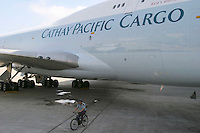 A security guard rides his bicycle past a Cathay Pacific Boeing 747 cargo plane in Xiamen, China..