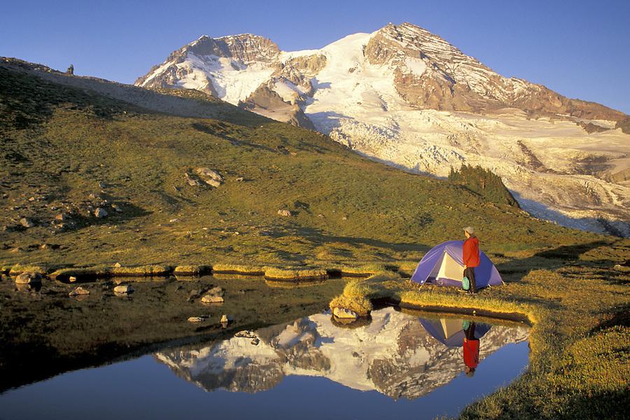 Woman setting up tent by lake below Mount Rainier, Mount Rainier National Park, Washington