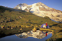 Woman setting up tent by lake below Mount Rainier, Mount Rainier National Park, Washington