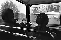 England. Greater Manchester. Salford. Rainy day, Traffic on the road. Family riding a double-decker bus. GM Buses. People on the move. The mother is seated by her husband while their daughter stands up. The father is smoking a cigarette. Salford is a city in the Metropolitan Borough of Salford in Greater Manchester. North West England is one of nine official regions of England. © 1990 Didier Ruef