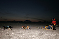 Doug Swingley leaves from the slough as the sun begins to rise on Monday morning at Unalakleet,   2005 Iditarod Trail Sled Dog Race.